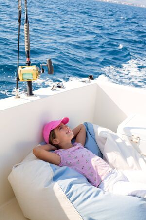 child girl sailing relaxed on boat deck enjoying a nap in blue sea photo
