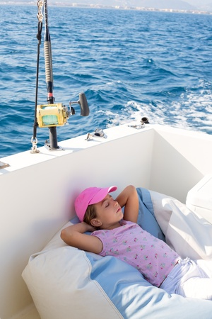 small boat: child girl sailing relaxed on boat deck enjoying a nap in blue sea Stock Photo