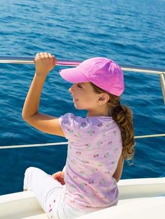 child happy girl sailing happy  boat with cap at blue sea ocean photo