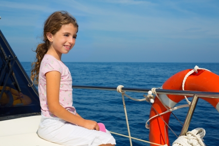 child happy girl sailing happy  boat  at blue sea ocean photo