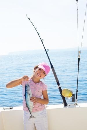 trolling: pesca ni�o ni�a en la celebraci�n de at�n barco bacoreta la captura de peces con ca�a y carretes para pesca de curric�n Foto de archivo