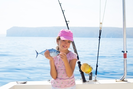 child little girl fishing in boat holding little tunny tuna fish catch with rod and trolling reels photo