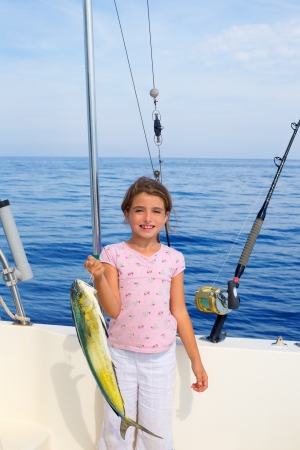 child girl fishing in boat with mahi mahi dorado fish catch with rod and trolling reels photo