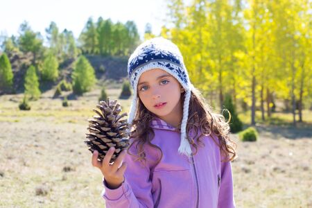 Child little girl holding pine cone in winter fall at nature outdoor photo