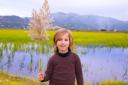 Blond kid girl outdoor holding spike in wetlands lake meadow photo