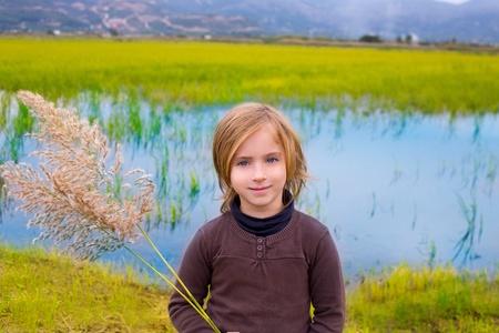 Blond kid girl outdoor holding spike in wetlands lake meadow photo