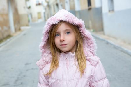 little town: Child girl tourist walking in traditional Spain village pink winter fur hood