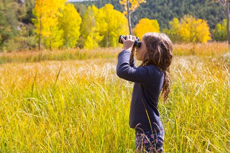 Explorer binocuar looking kid girl in yellow autumn nature outdoor photo