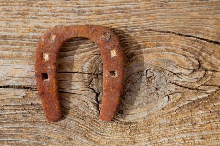 Antique horseshoe luck symbol rusted on vintage wood background Stock Photo - 17614284