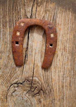 barn door: Antique horseshoe luck symbol rusted on vintage wood background