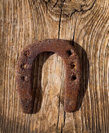 Antique horseshoe luck symbol rusted on vintage wood background Stock Photo - 17614285
