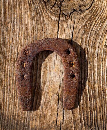 Antique horseshoe luck symbol rusted on vintage wood background Stock Photo - 17614285
