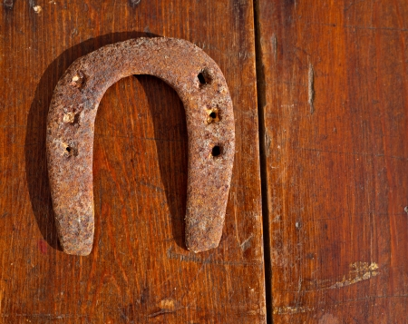 Antique horseshoe luck symbol rusted on vintage wood background photo