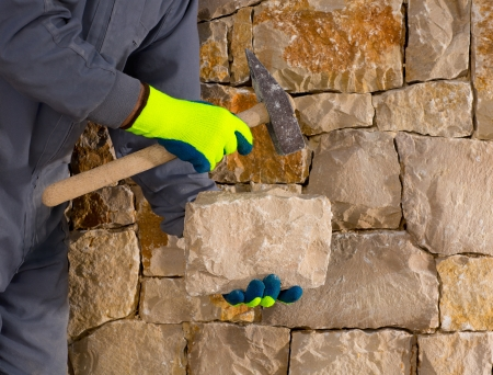 laborers: stonecutter mason with hammer and stone building a masonry stone wall Stock Photo