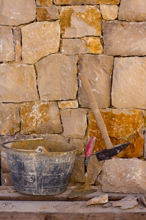 stone work: Hammer mason tools of stonecutter masonry work in a contruction stone wall
