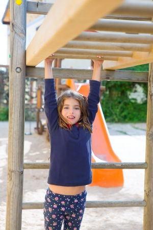 kid girl playing in playground  hanging from wood bars smiling happy photo