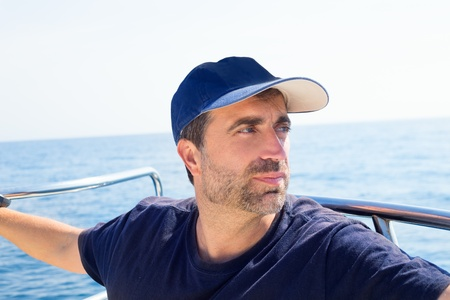 Sailor man at boat bow with cap looking away the sea while sailing Stock Photo - 17600686