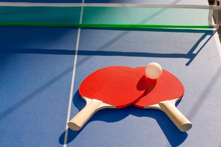 pingpong: tenis de mesa dos paletas y la bola blanca sobre azul Foto de archivo