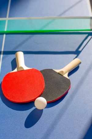 paddles: table tennis ping pong two paddles and white ball on blue board