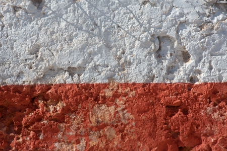 Aged whitewashed wall with red grunge paint wheatered photo