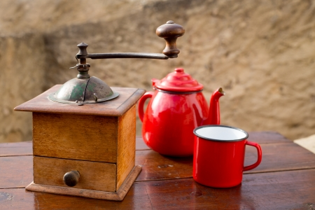 retro old coffee grinder with vintage teapot and red cup photo