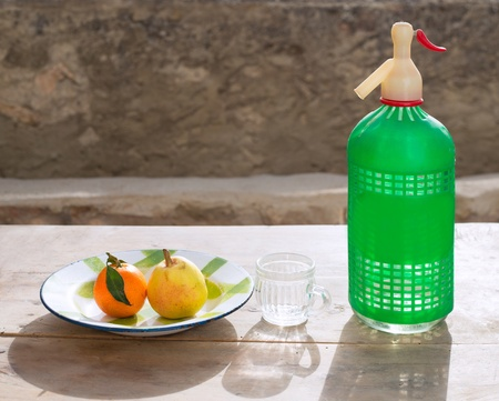 dish disk: fruits tangerine and pear in vintage porcelain dish with retro soda bottle Stock Photo