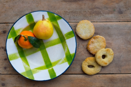 plateful: fruits tangerine and pear in vintage porcelain dish with handmade biscuits