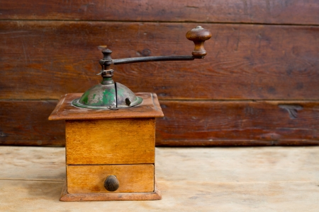 trundle: retro old coffee grinder with vintage wooden background Stock Photo