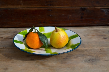 dish disk: fruits tangerine and pear in vintage porcelain dish plate on retro wood table