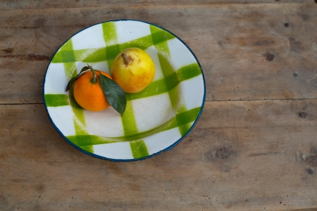 plateful: fruits tangerine and pear in vintage porcelain dish plate on retro wood table