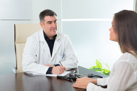 Doctor man and patient woman on hospital office talking on desk Stock Photo - 19636943