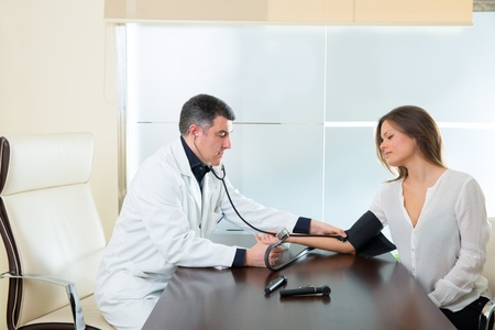 Doctor man checking blood pressure cuff on woman patient arm on hospital office Stock Photo - 19636938