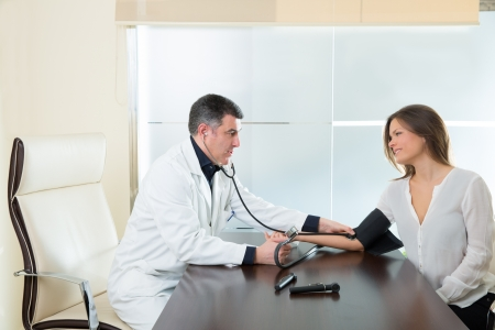 blood pressure cuff: Doctor man checking blood pressure cuff on woman patient arm on hospital office Stock Photo