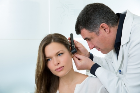 Doctor ENT checking ear with otoscope to woman patient at hospital photo