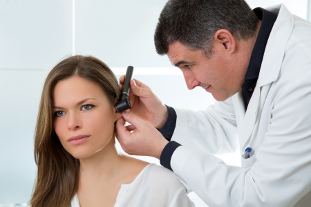 otoscope: Doctor ENT checking ear with otoscope to woman patient at hospital Stock Photo