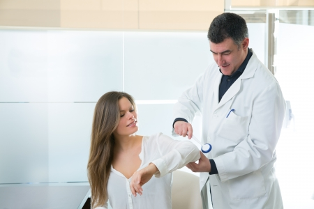 female elbow: Doctor checking elbow with reflex round hammer to woman patient in hospital Stock Photo