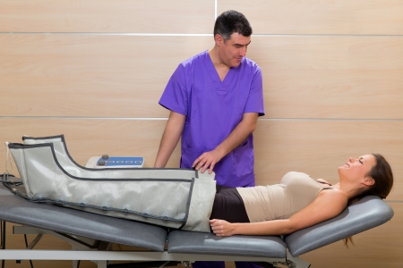 Doctor checking legs pressotherapy machine on woman patient in hospital bed photo