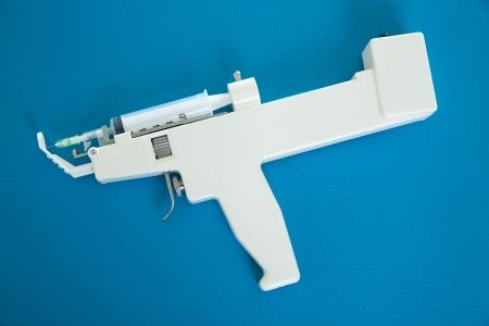 fat burning: mesotherapy gun electronic with syringe on blue background
