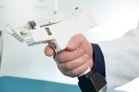 mesotherapy gun electronic with syringe on doctor hands photo
