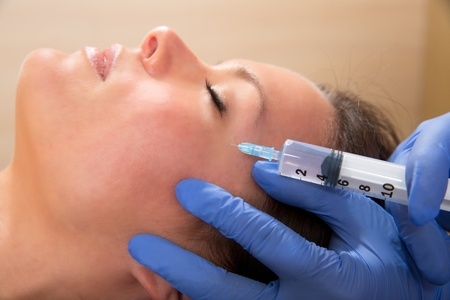 Anti aging facial mesotherapy with syringe closeup  on woman face photo