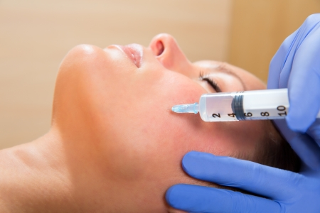 facial hygiene: Anti aging facial mesotherapy with syringe closeup  on woman face