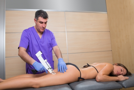 latex: mesotherapy gun therapy for cellulite doctor with woman leg thigh Stock Photo