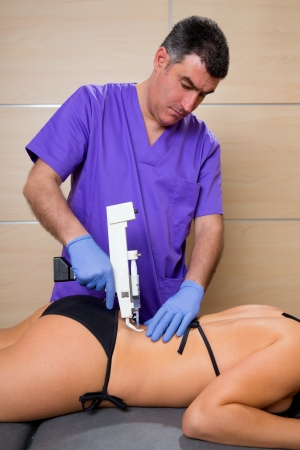 latex girl: Back lumbar mesotherapy gun doctor therapy with woman patient on bed Stock Photo