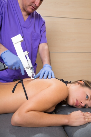 Back lumbar mesotherapy gun doctor therapy with woman patient on bed photo