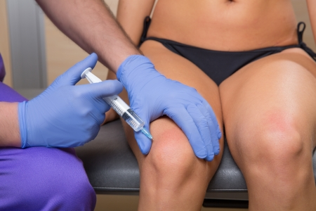 injection: mesotherapy biopuncture doctor with syringe on woman leg Stock Photo