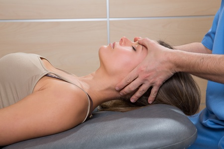 facial massage: facial reflexology doctor hands in woman face therapy profile view Stock Photo