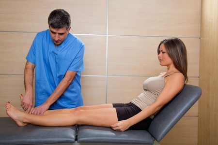 Ankle joint mobilization therapy of doctor man to patient woman in hospital photo