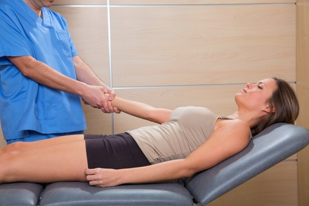 fascial therapy doctor pulling patient woman arm at hospital photo