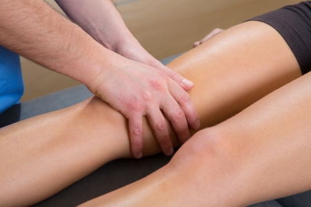 alternative therapies: lymphatic drainage massage therapist hands on woman leg knee Stock Photo