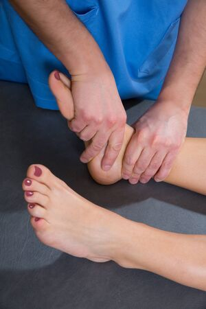 Ankle joint mobilization therapy of doctor man to patient woman in hospital Stock Photo - 19616616